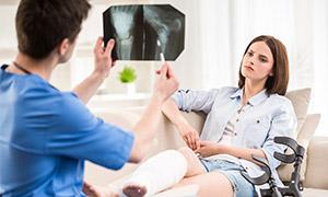 врач изучает рентгеновский снимок пациентки с переломом ноги